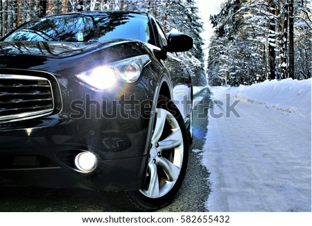 Luxury black crossover made a stop on the winter road in the forest.