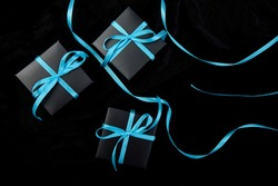 Luxury black gift boxes with blue ribbon on shine black background. Christmas, birthday party presents. Father Day. Flat lay. Copy space. Top view.