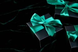 Luxury black gift boxes with green ribbon on shine velvet background. Christmas, birthday party presents. Father Day. Flat lay. Copy space. Top view.