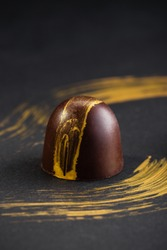 Luxury bonbons painted with gold on black background. Exclusive handmade chocolate candy. Product concept for chocolatier
