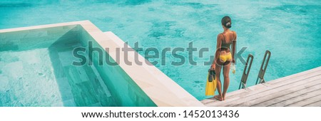 Luxury Bora Bora resort woman going snorkeling from overwater bungalow panoramic. Tahiti paradise destination vacation. #1452013436
