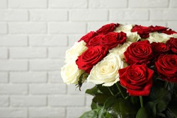 Luxury bouquet of fresh roses near white brick wall, closeup. Space for text