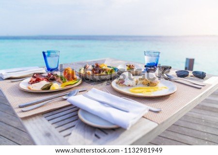 Luxury breakfast food on wooden table, with beautiful tropical Maldives island background, morning time holiday vacation concept. #1132981949