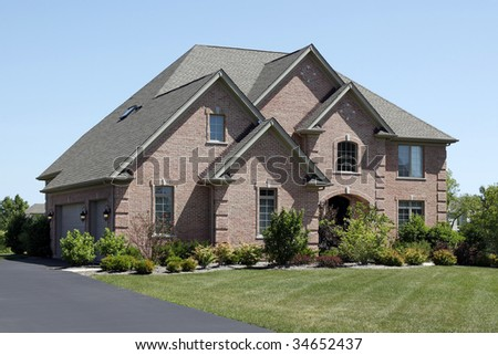 Luxury brick home in suburbs with cedar shake roof
