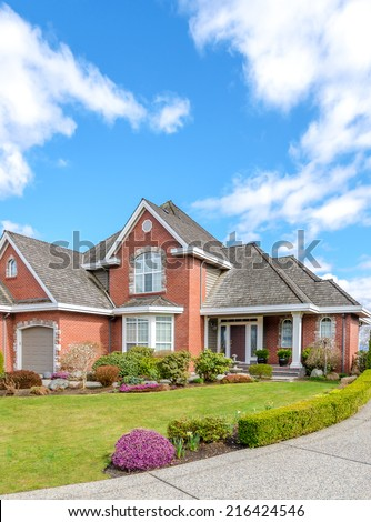 Luxury brick house with a two-car garage and beautiful landscaping on a sunny day in Vancouver, Canada. #216424546