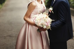 luxury bride and groom holding hands and gorgeous pink and white bouquet, rich wedding couple, tender romantic moment at garden with blossoms