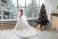 Luxury bride in wedding dress for Christmas near the large panoramic window. Luxury bride in wedding dress for Christmas. Charming bride in an elegant wedding dress. Bride in luxurious suites.