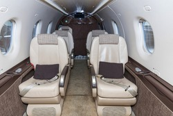 Luxury bright leather interior of a modern commercial airplane. Inside of a small business turboprop aircraft.