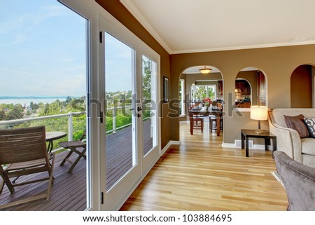 Luxury brown living room with hardwood floors and large balcony.