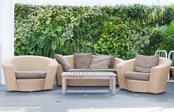Luxury brown rattan patio garden and hotel furniture chairs and table with the earth-tone pillow set on it and green bush background for recreational, relaxation and resting.