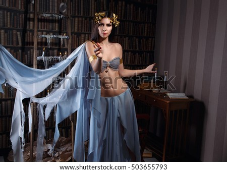 Stock Photo Luxury brunette in wreath of leaves. A seductive dance of a woman in Greco-Roman clothing. Bohemian style. Fantastic shooting. Fashionable toning. Creative color.