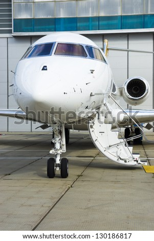 Luxury Business Private Jet plane at airfield toned in blue
