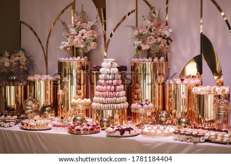 Luxury candy bar on golden wedding. Candy bar decorated by flowers standing of festive table with deserts, and cakes, strawberry tartlet, cupcakes and macarons. Wedding. Reception Tartlets