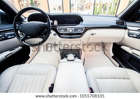 Luxury car interior. Steering wheel, shift lever and dashboard. #1055708105