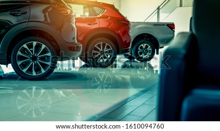 Luxury car parked in modern showroom. Auto leasing business. Car dealership concept. Closeup wheel of red shiny car show in showroom. Automotive industry. Auto glass coating and shinning business.