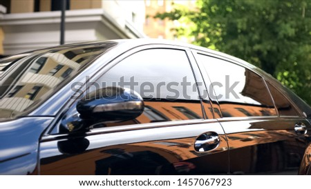 Luxury car with tinted glass standing at parking, reflection of businessman ストックフォト ©