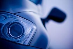 Luxury car xenon headlight on a blurry background. Car head light in focus