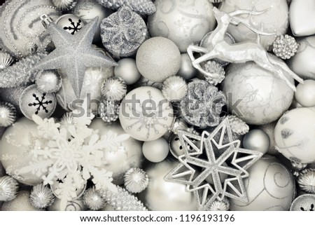 Luxury Christmas silver and white decorations with star, reindeer, snowflake, gift box, balls and pine cone baubles forming an abstract background. Traditional greeting card for the holiday season.   #1196193196