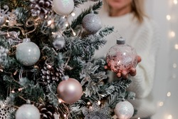 Luxury Christmas tree with white, silver and pink balls,  snow and glowing garland. Girl holding a ball