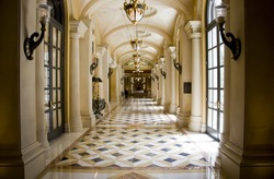 Luxury classic colonnade corridor with marble floor and row of lusters