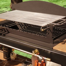 luxury Combo BBQ Grill. Backyard Kitchen Table With BBQ Charcoal Grill Appliance. Family Garden Party Barbecue Grill, Closeup View, Green Backyard Lawn In The Background.