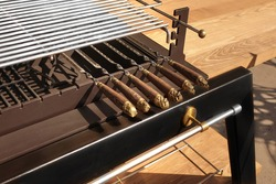 luxury Combo Grill Table. Outdoor Backyard Kitchen Table With BBQ Charcoal Grill Appliance. Family Garden Party Barbecue Grill, Closeup View, Green Backyard Lawn In The Background.