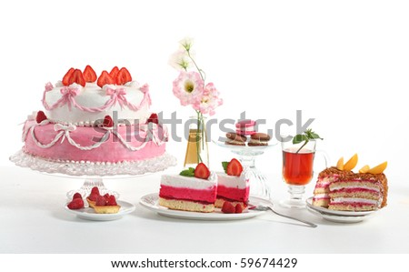 Luxury composition with a pie, tea, fruit cakes and flowers.