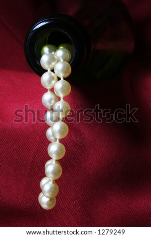 Luxury concept with pearls flowing out of a champagne bottle against a red drape