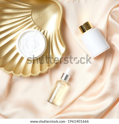 Luxury cosmetic set and golden seashell on peach color silk background. Skincare beaut products design, branding. Photo stock ©