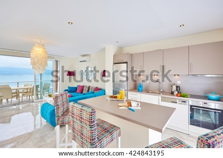 Luxury cozy light kitchen interior with fancy modern color furniture, marble floor,  terrace and sea view in Bodrum Turkey  with sea and terrace and food served -  Sucessful sea life concept