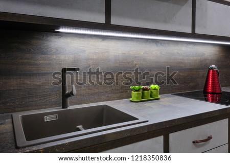 Luxury cozy modern dark brown kitchen interior, induction stove, minimalistic clean design