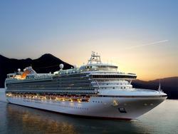 Luxury cruise ship sailing from port on sunrise.