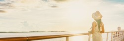 Luxury cruise ship vacation woman elegant tourist woman watching sunset on balcony deck of Europe mediterranean cruising travel destination. Summer vacation cruiseship banner panorama.