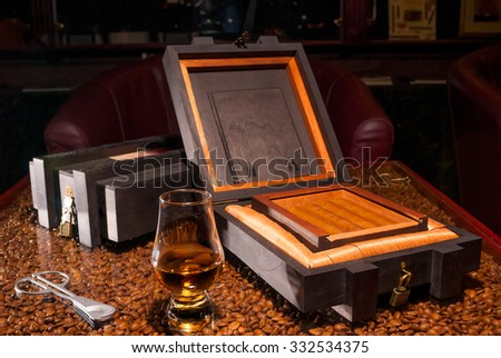 luxury Cuban cigars in a box and a glass of alcohol