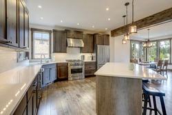 Luxury dark wood rich kitchen interior with white subway tiles backsplash and quarts countertop.