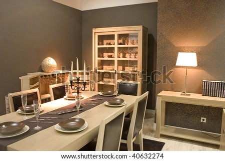 Luxury dining room and dinig table with glasses, dishes and furniture.