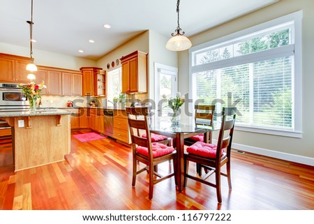 Luxury Dining room and kitchen with red cherry wood and large window.