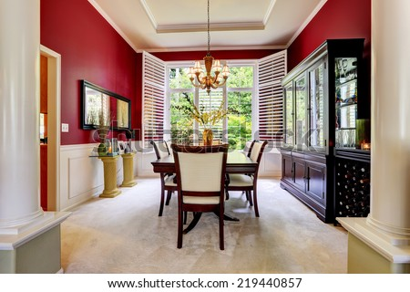 Luxury dining room with bright red wall and white french window.