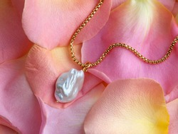 Luxury elegant baroque pearl pendant with golden chain on delicate pink yellow rose petals. Close-up shot