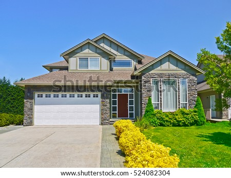 Luxury family house with concrete driveway to the garage on blue sky background #524082304