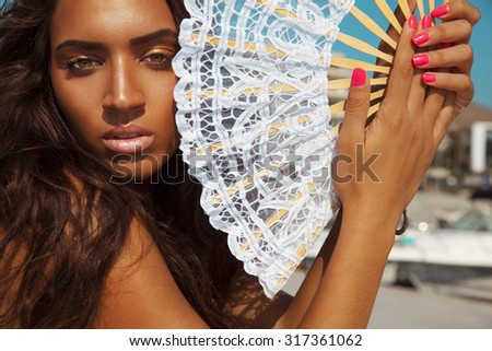 Luxury fashion style portrait of Latin woman with fan. Manicure nails . Cosmetics and make-up . Toned in warm colors. Horizontal shot.