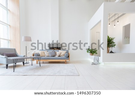 Luxury fashionable modern design studio apartment with a free layout in a minimal style. very bright huge spacious room with white walls and wooden elements. sitting area with fireplace Foto stock ©