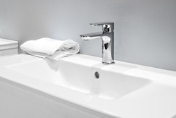 Luxury faucet mixer and white towel on a white sink in a beautiful gray bathroom. Sanitary prevention antivirus concept.