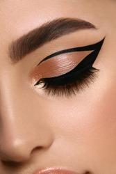 luxury female make-up close-up with eyeliner and golden eye shadow, glamourous cat eye mua, evening style