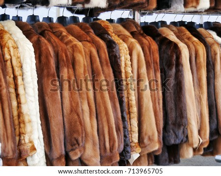 Luxury fur coats hanging on rack, various colors of mink, fox and sheep fur for sale at the market