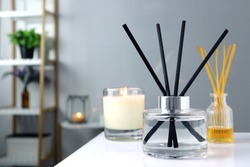 luxury glass aroma scent reed diffuser bottle is used as air freshener on the table with scented candle in the nice white living room to creat relax , cozy and clean ambient and for decoration