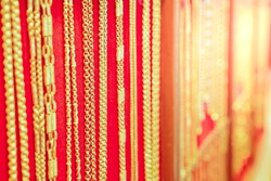 Luxury gold necklaces on red flannel background with morning sunlight. Golden necklaces in gold jewelry store. It can be used for presentations about gold and also use as a background for the desktop.