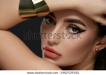 luxury golden and black make-up on brunette face with golden jewelry, evening glamour style, fashion diva looking to the camera