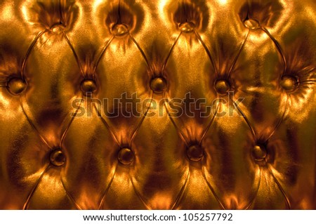 Luxury golden leather upholstery of a magnificent sofa close-up background