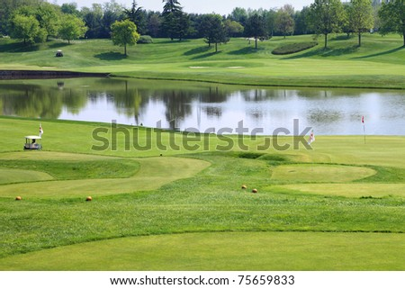 luxury golf club with flags and lake in background